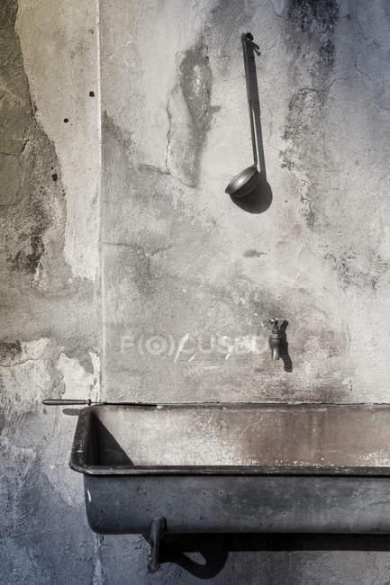 Wandtrog und Wasserhahn mit Schöpfkelle — Stockfoto