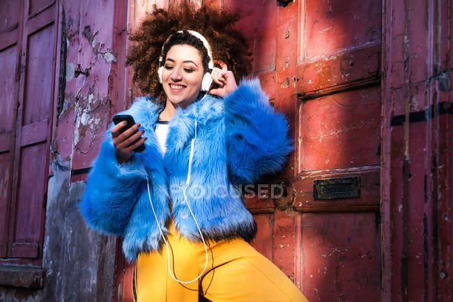 Donna in strada ascoltare musica attraverso le cuffie su smartphone — Foto stock
