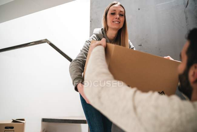 Couple passing cardboard boxes — Stock Photo