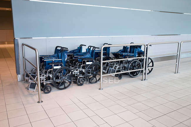 Front view of wheelchairs placed in rows at airport — Stock Photo