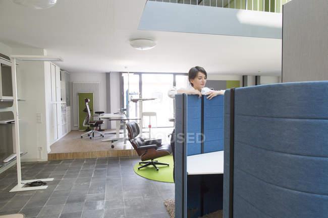 Responsabile di vendita femmina giovane che osserva sopra il divisorio per ufficio in negozio di mobili ufficio — Foto stock