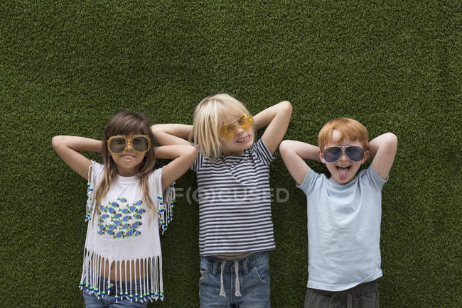 Children in front of artificial turf wall in sunglasses — Stock Photo