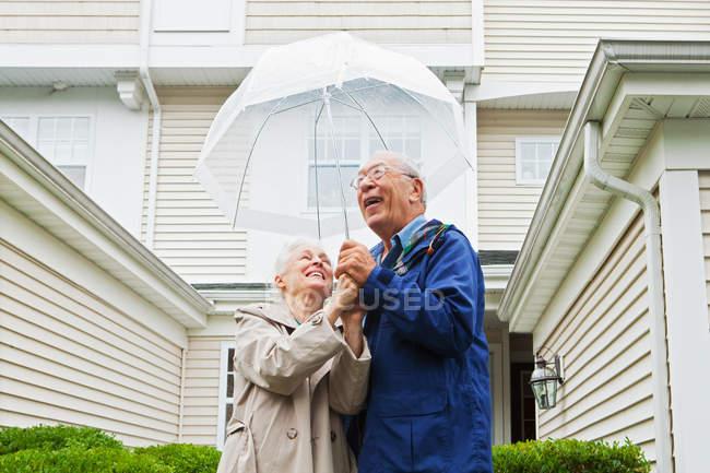 Casal sênior segurando guarda-chuva fora — Fotografia de Stock