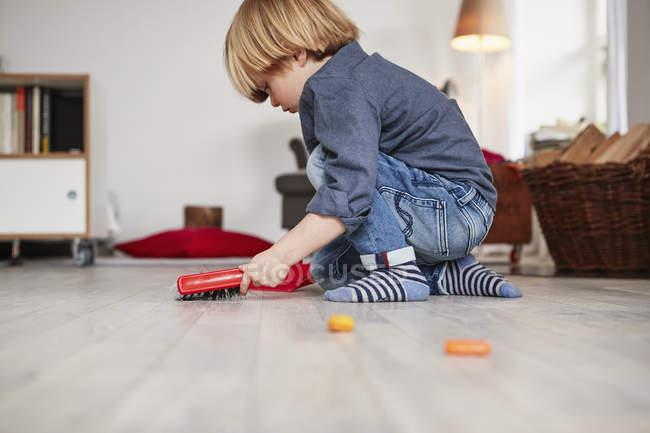 Хлопчик грає з іграшкою совок і пензля — стокове фото