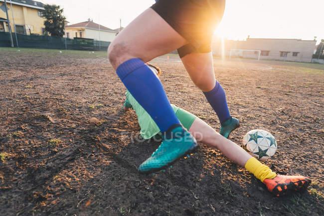 Footballeurs jouant sur le terrain au coucher du soleil — Photo de stock