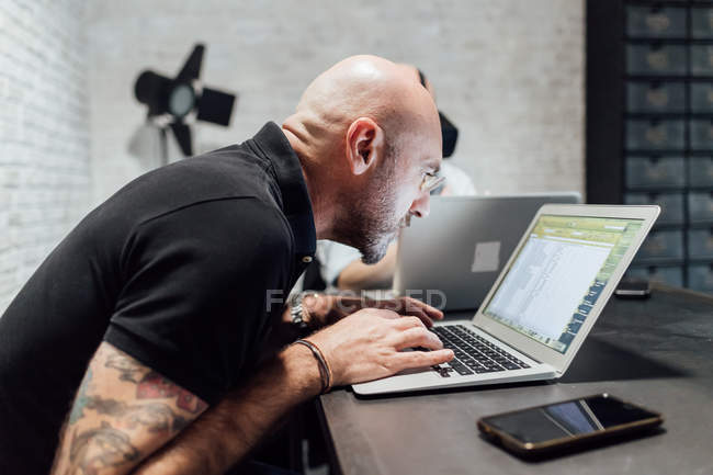Man at desk peering in laptop in office — Stock Photo