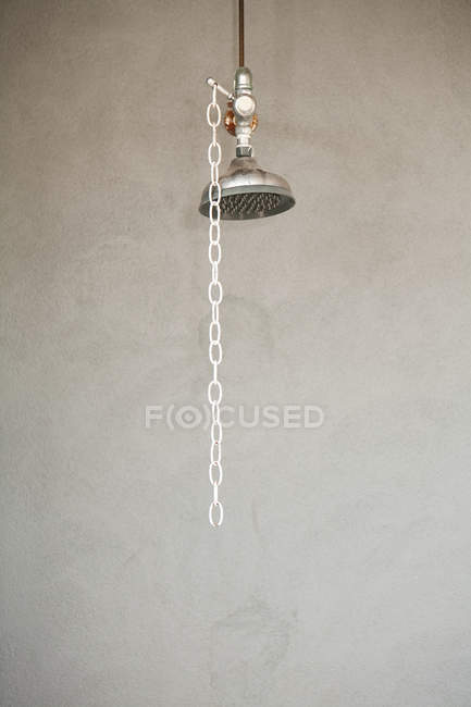 Duschkopf mit Kette auf grauem Wandhintergrund — Stockfoto