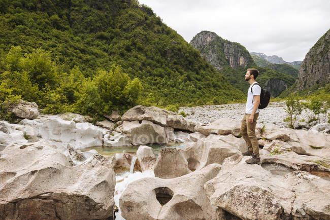 Hombre de pie sobre rocas y mirando hacia otro lado, Malditas montañas, Theth, Shkoder, Albania, Europa - foto de stock