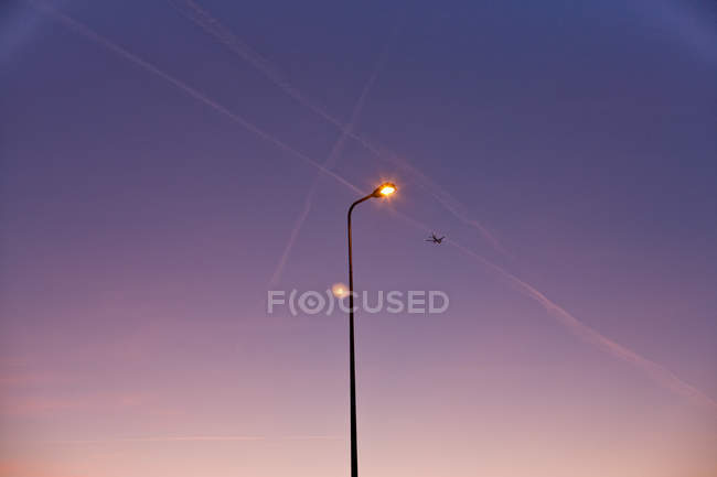 Lamppost under lilac sky with traces of airplanes — Stock Photo