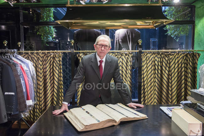 Senior tailor with handmade swatch book in traditional tailor shop — Stock Photo