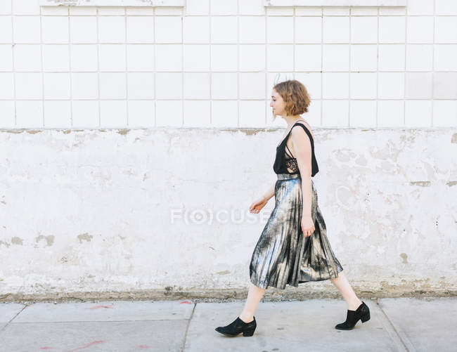 Side view of Woman in metallic skirt walking on street — Stock Photo