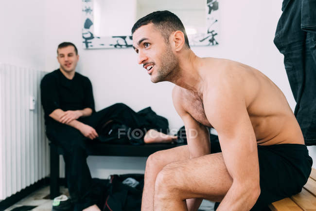 Men on benches in gym changing room — Stock Photo