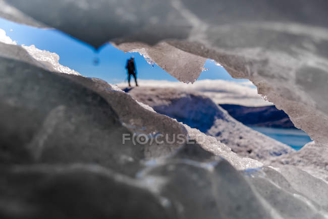 Guide seen through hole in ice on glacier in South Green — Stock Photo