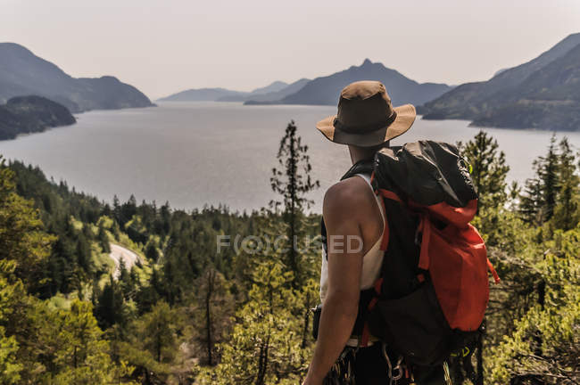 Scenic view of male Hiker enjoying view of lake and mountains, Squamish, Canada — Stock Photo