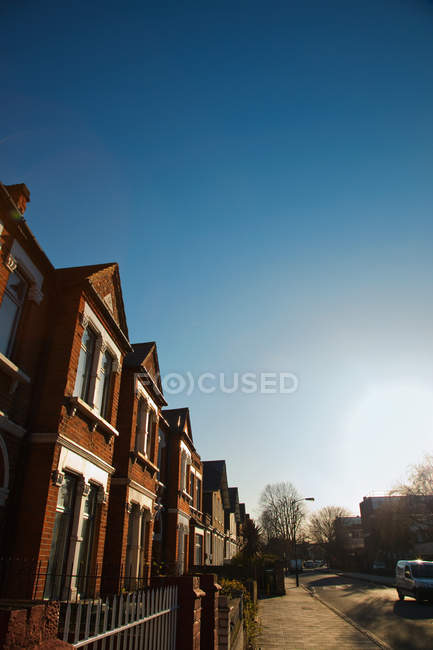 View of brown houses on street against blue sky — Stock Photo
