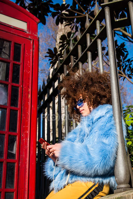 Woman by traditional red telephone box texting on smartphone — Stock Photo