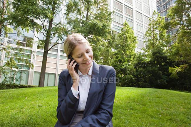 Joven mujer de negocios hablando por teléfono celular al aire libre - foto de stock