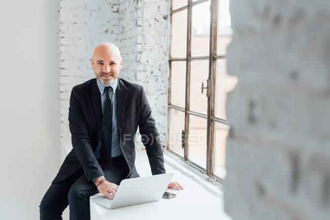 Uomo d'affari con computer portatile seduto sul davanzale della finestra e guardando in macchina fotografica — Foto stock