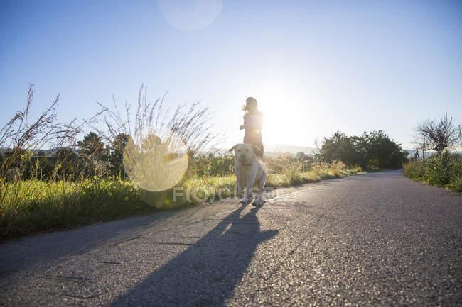Mujer joven corriendo por carretera rural con perro - foto de stock