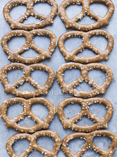Close up of pretzels with salt on cookie sheet — Stock Photo