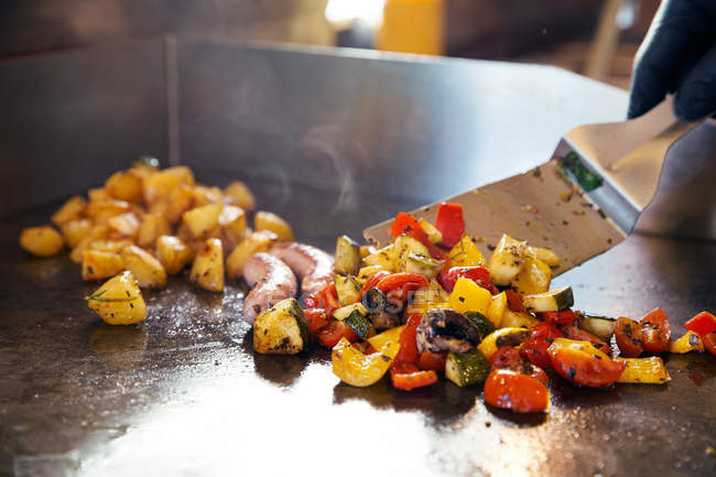 Cropped image of chef preparing vegetables on flat top grill — Stock Photo