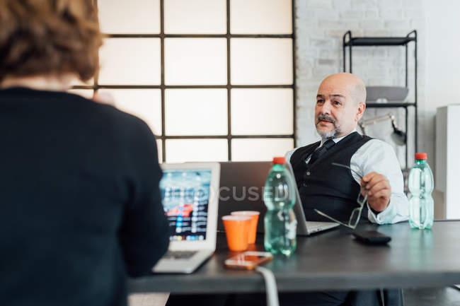 Colleghi in ufficio parlando e utilizzando computer portatili — Foto stock