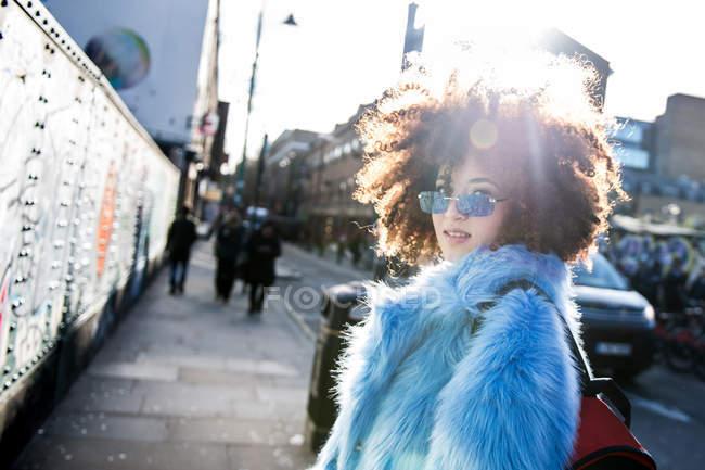 Ritratto di donna con capelli afro che indossa pelliccia guardando la macchina fotografica — Foto stock
