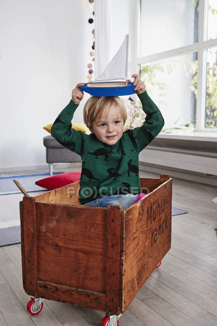 Young boy sitting in toy box and holding toy boat on head — Stock Photo