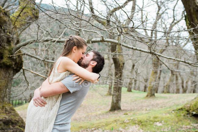 Romantisches Paar küssen und umarmen im park — Stockfoto