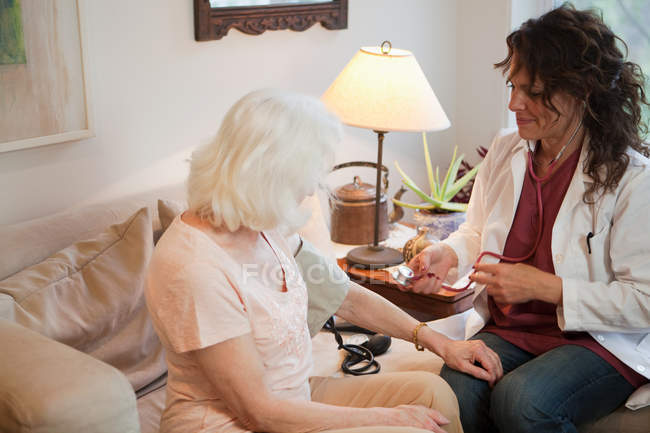 Médecin prenant la pression artérielle de la femme âgée — Photo de stock