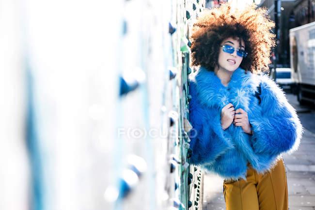 Ritratto di donna con capelli afro che indossa pelliccia contro muro — Foto stock