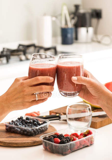 Cropped image of friends clinking with glasses of smoothies at home — Stock Photo