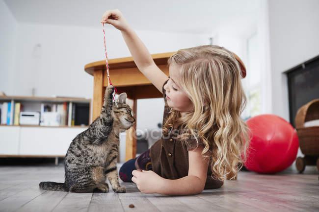 Jovem, deitado no chão e brincar com o gato — Fotografia de Stock