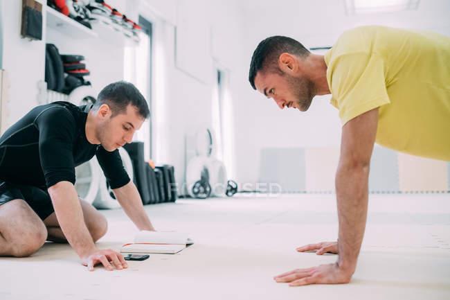 Mann mit Trainer tun Push Ups — Stockfoto