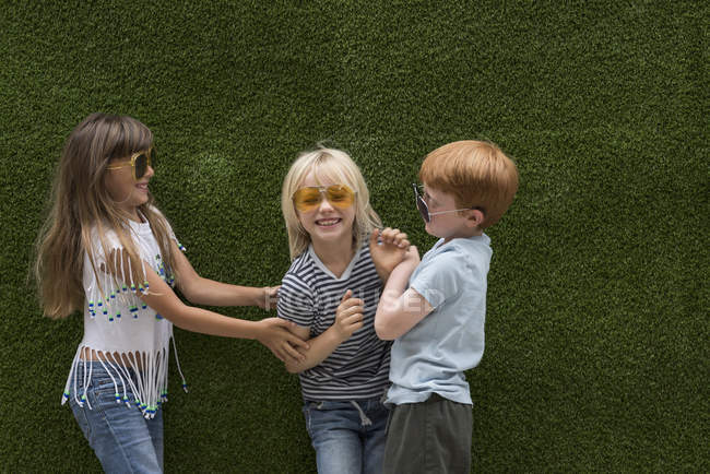 Children in front of artificial turf wall playing on tickle — Stock Photo