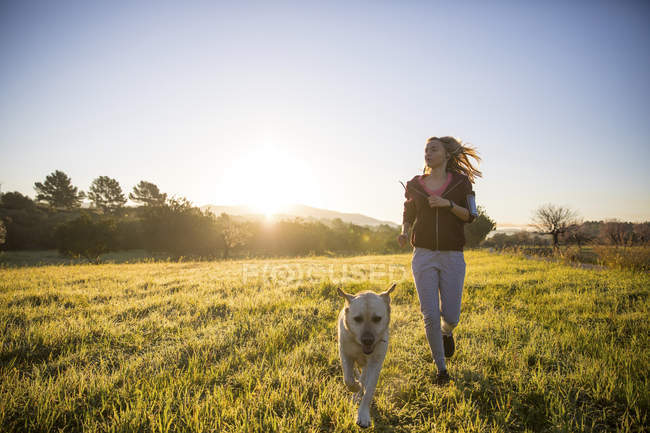 Giovane donna che corre attraverso il campo con il cane — Foto stock