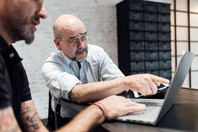 Colleagues talking and looking at laptop together — Stock Photo