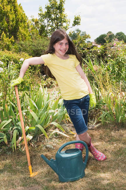 Portrait of girl in garden with rake and watering can — Stock Photo