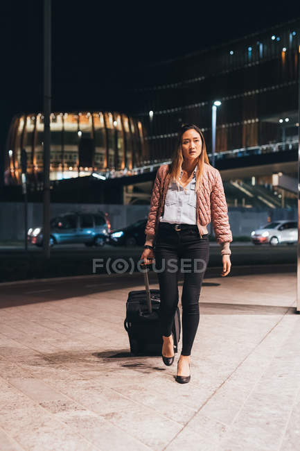 Woman walking outdoors at night with wheeled suitcase — Stock Photo