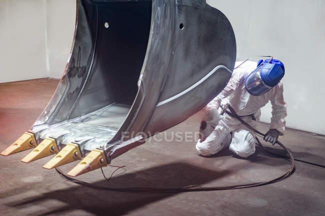 Homem que pinta o balde do escavador na cabine de pulverização na fábrica de engenharia — Fotografia de Stock