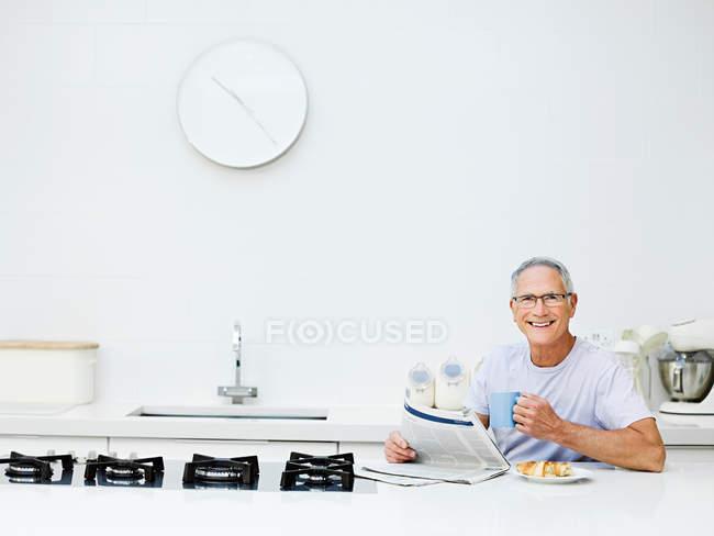 Senior homme prenant son petit déjeuner et la lecture des journaux — Photo de stock