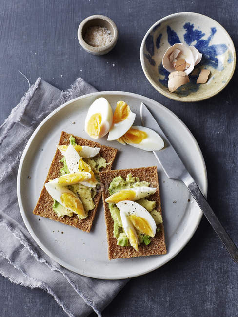 Still life of rye crackers with boiled sliced eggs on plate — Stock Photo