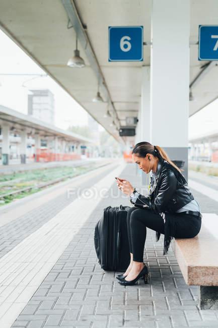 Femme assise sur le quai du train et utilisant un smartphone — Photo de stock