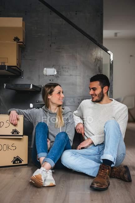 Couple assis avec des boîtes en carton, déménagement — Photo de stock