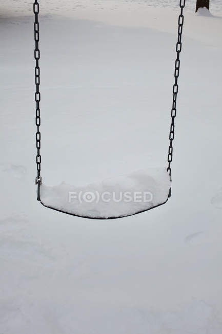 View of snow covered swing, close-up — Stock Photo