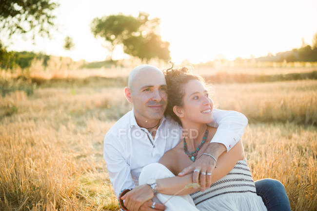 Portrait of couple hugging in field — Stock Photo