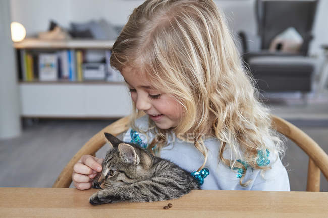 Portrait of young girl stroking cat — Stock Photo