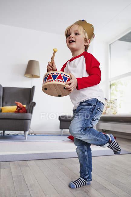 Молодий хлопчик в картонні корони побиття іграшка барабан — стокове фото