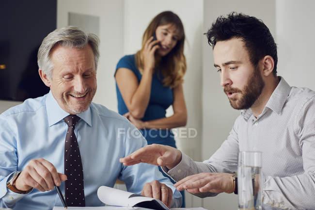 Trois collègues de travail au bureau à la réunion — Photo de stock