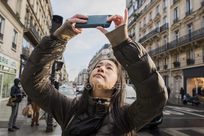 Mulher jovem asiática levando tiro smartphone na rua da cidade, Paris, França — Fotografia de Stock
